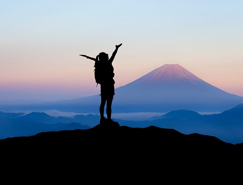 Silhouette of woman raising her hands on top of mountain during daytime
