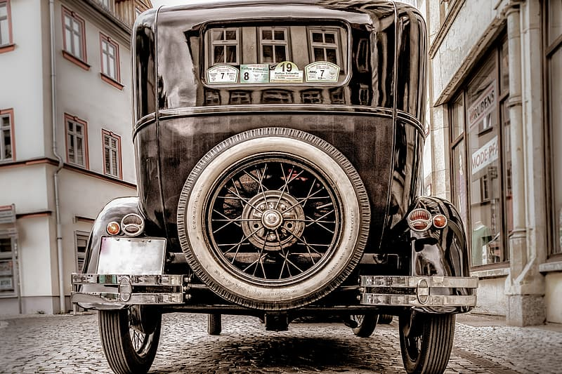 Black vintage car in front of white concrete building during daytime