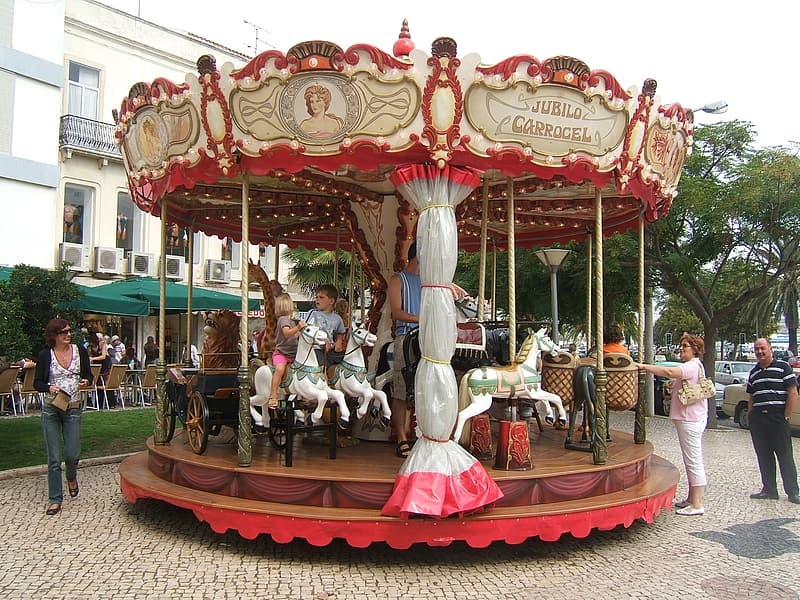 Children riding on gray and red carousel