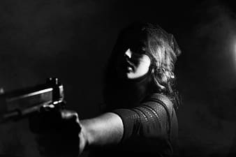 Grayscale photo of person holding pistol