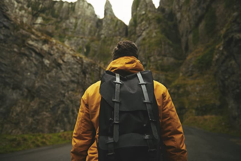 Man wearing yellow hoodie and backpack standing in-front of a rocky mountain