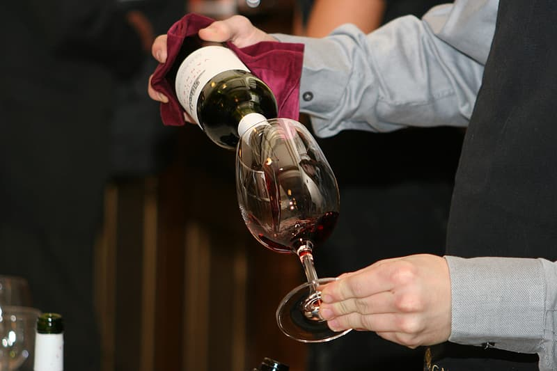 Person pouring wine in goblet