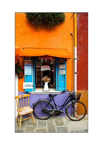 Woman in white long sleeve shirt standing beside blue bicycle during daytime