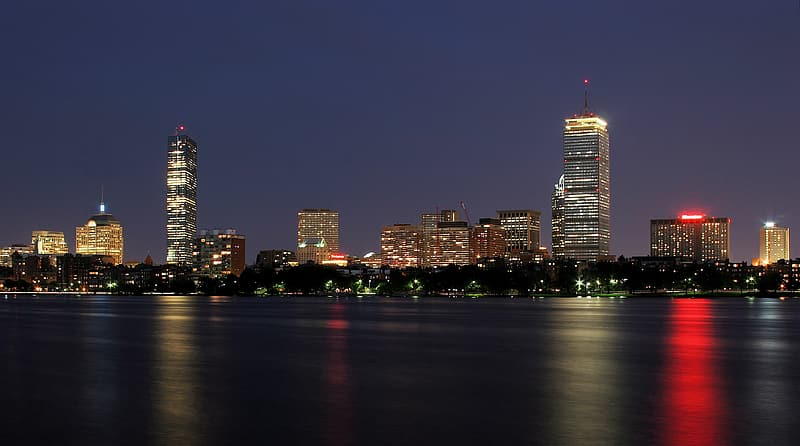Photo of high-rise buildings near body of water during night time