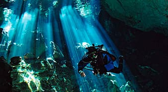 Person diving underwater with sunlight