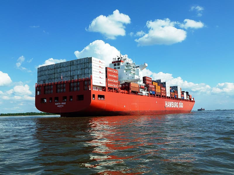 Red cargo ship on body of water