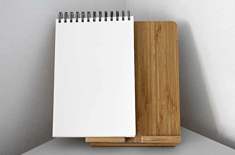 White sketch pad on brown wooden board