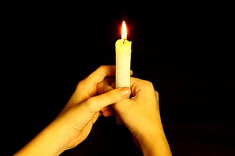 Person holding white candle