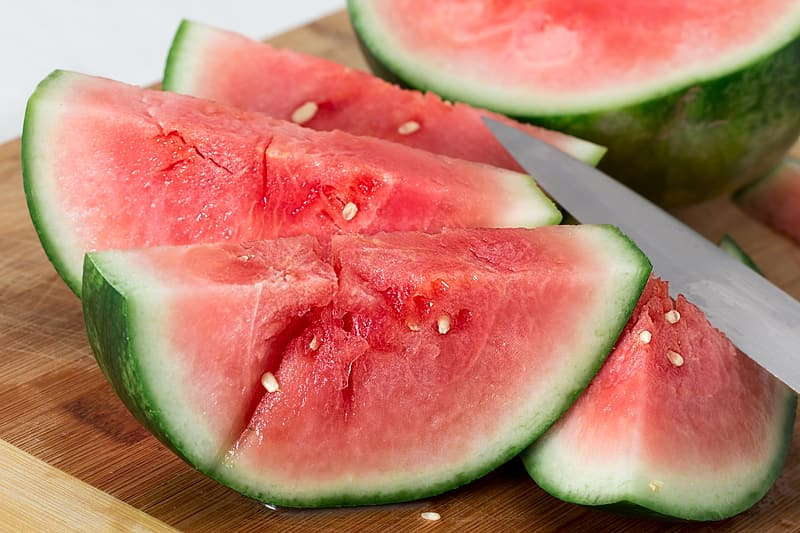 Sliced water melon on brown wooden chopping board