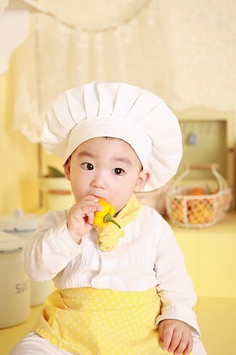 Selective focus photography of boy in chef costume
