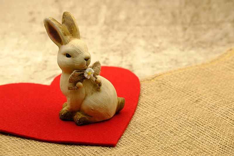 Brown rabbit figurine on red heart pillow