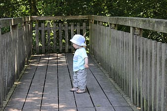 Child in white hoodie and blue pants walking on gray wooden pathway