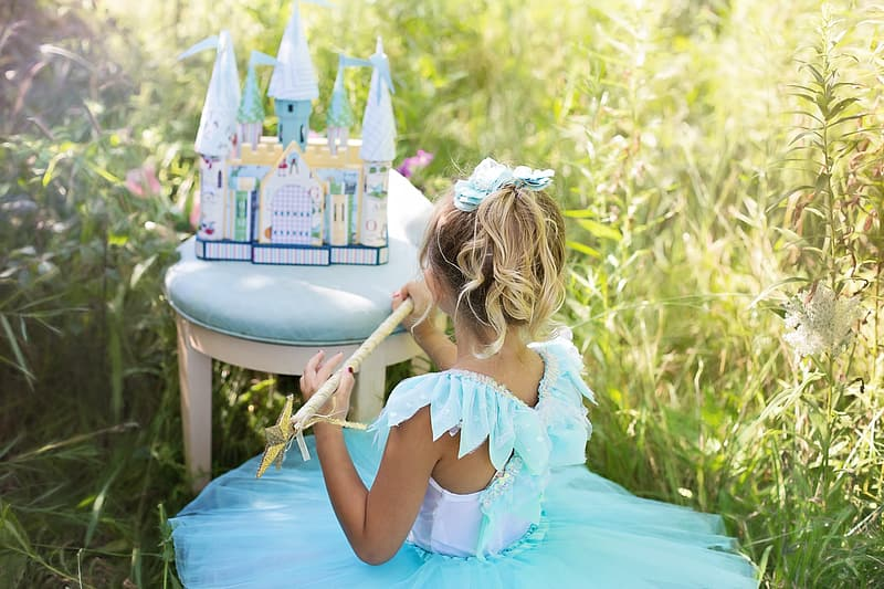 White and blue castle toy and girl wearing blue and white sleeveless tutu dress at daytime