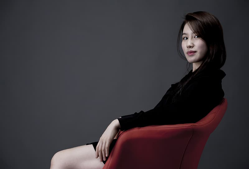 Woman wearing black long-sleeved shirt sitting on red tub chair