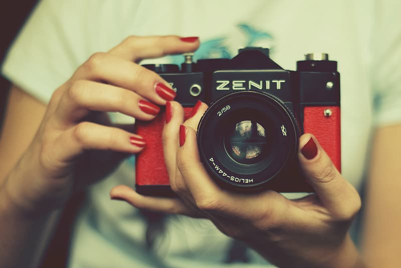 Person holding red and black Zenit SLR camera