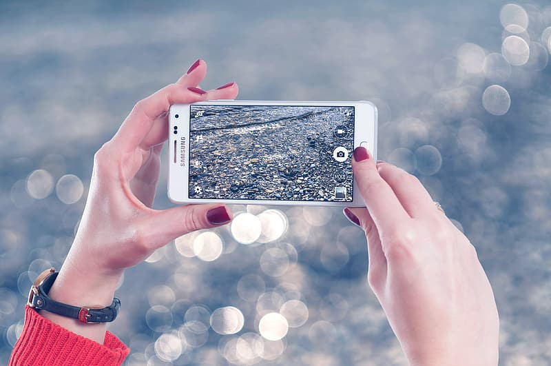 Woman holding up white Samsung Android smartphone taking photo