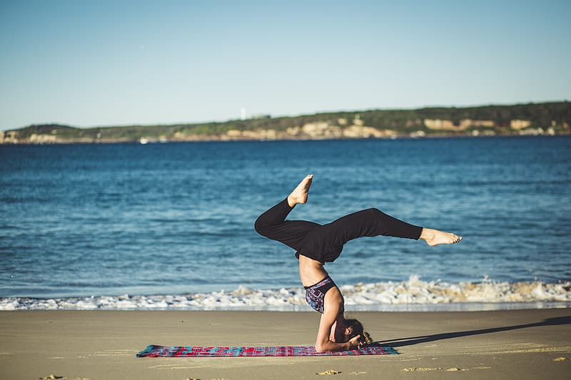 Woman in black long sleeve shirt and black pants doing yoga on beach shore during daytime