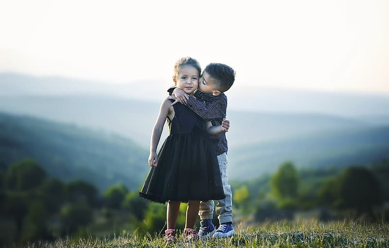Selective focus photography of boy kissing girl's cheek