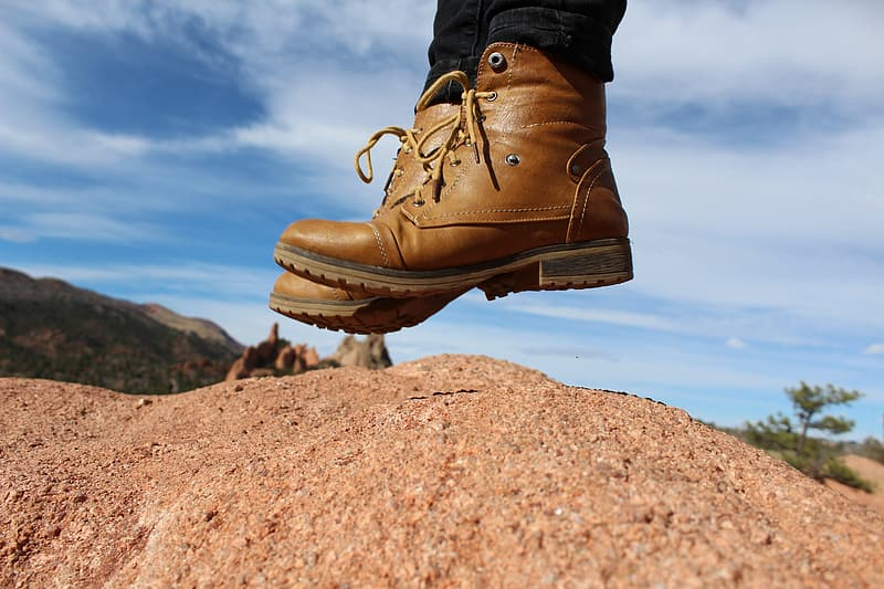 Person wearing brown leather cap-toe chunky heel combat boots jumping over brown soil