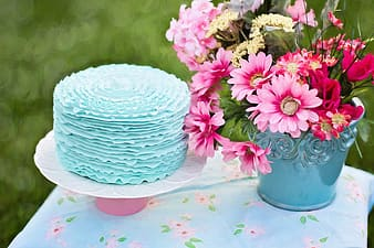 Pink petaled flower with green vase on table