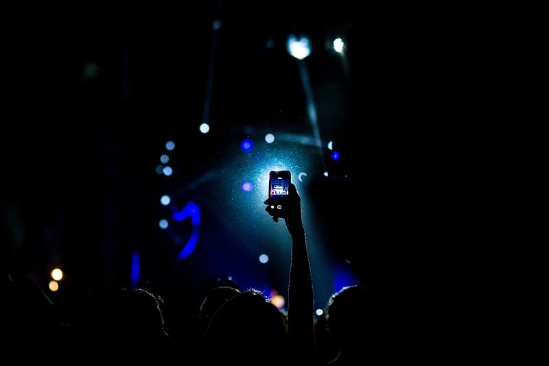 Person taking a video of concert