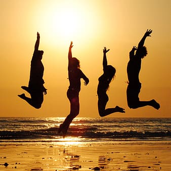 Silhouette of four people jumping