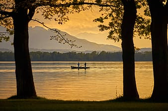Silhouette of person sitting on bench near lake during sunset
