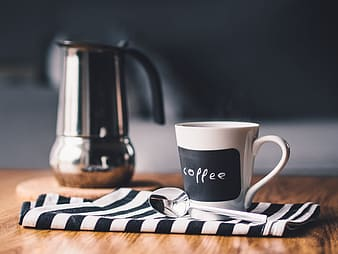 White and black coffee labeled ceramic mu near stainless pitcher