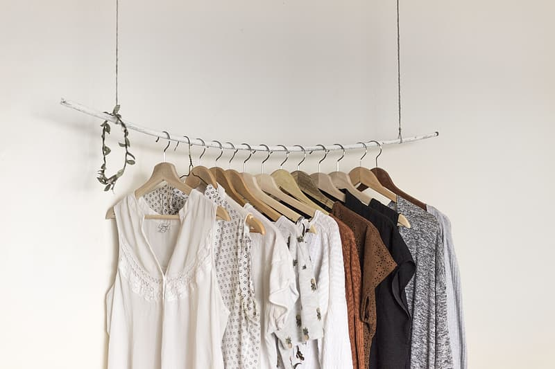 Hanged assorted-color clothes beside white paint wall room