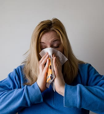 Woman pressing her nose with facial tissue