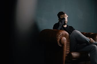 Man in black long sleeve shirt sitting on brown leather armchair
