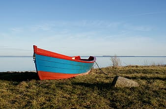Wooden boat on field of grass fronting sea
