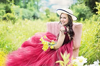 Woman wearing pink sleeveless dress with white sun hat sitting on brown fabric sofa chair near green grass field while taking a photo