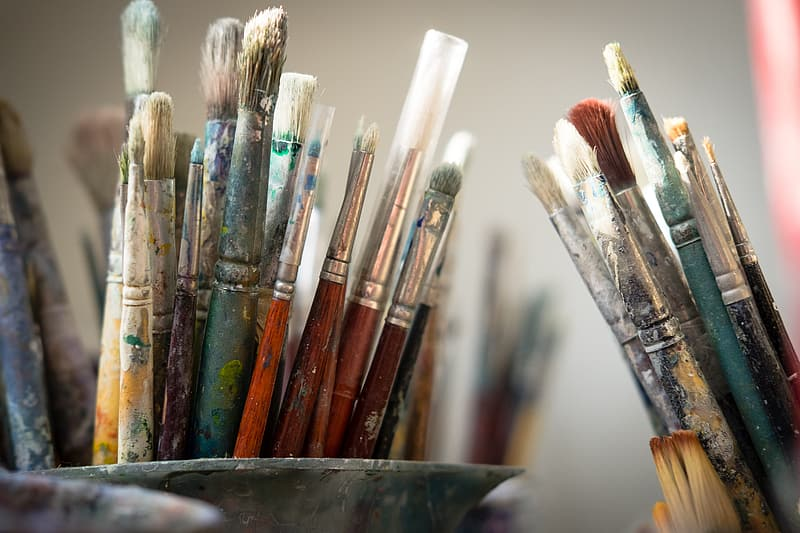 Brown and green paint brushes in blue glass container