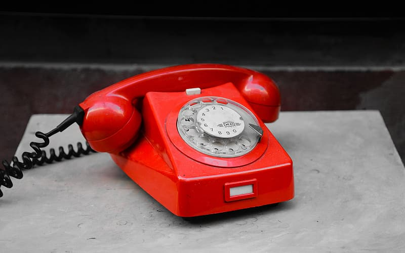 Red rotary telephone on gray surface