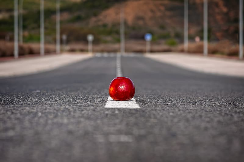 Selective focus of red apple on road