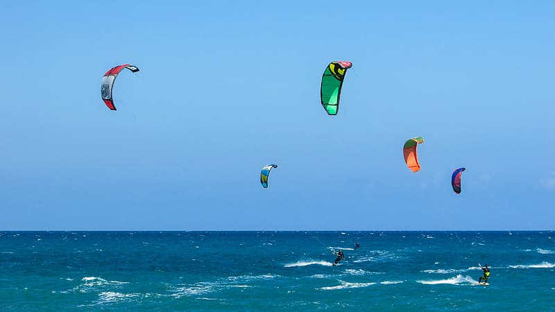 People parachuting over body of water during daytime
