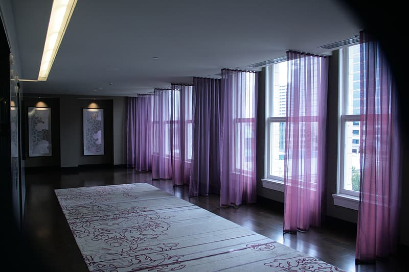 Room with purple curtains and floral area rug