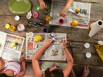 Girls painting easter eggs on the table