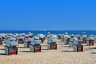 Red and white booths on seashore during daytime