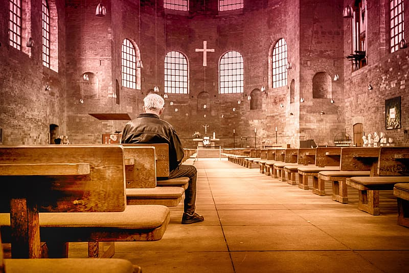 Man sitting on church bench