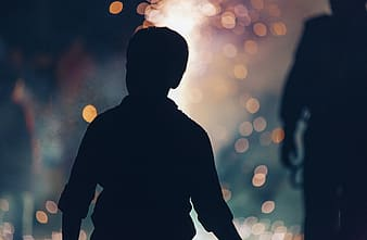 Silhouette photo of boy with bokeh background