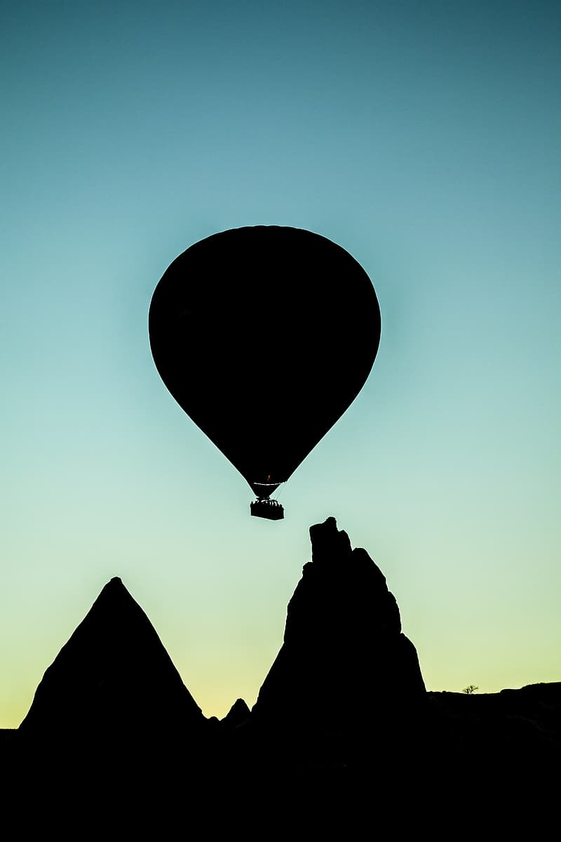 Silhouette of hot air balloon flying distance with mountains at blue hour
