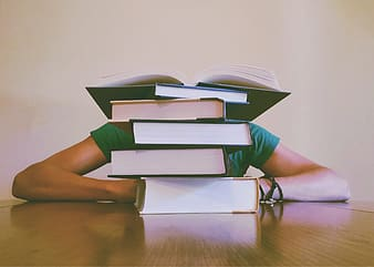 Person sitting in front of piled of books on top of table