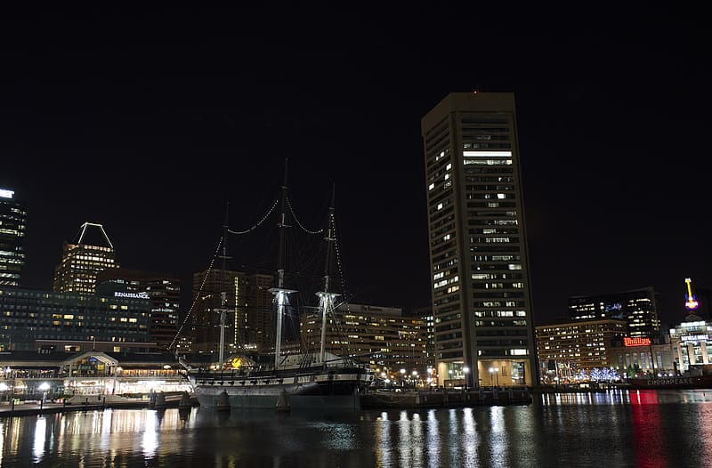 Sail boat near buildings during nighttime