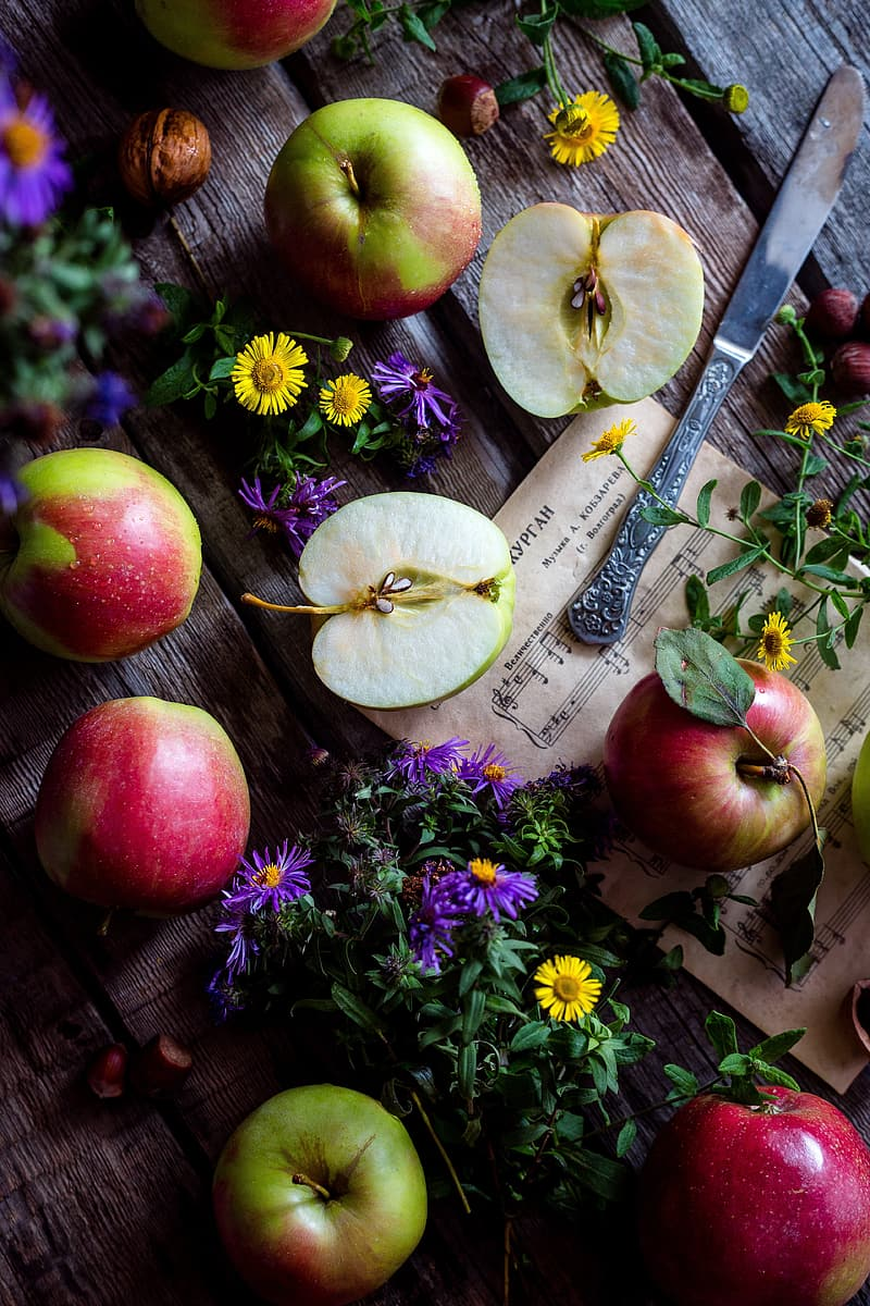 Red and green apples beside flowers