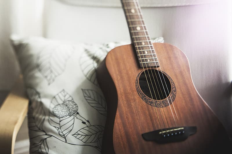 Selective focus photo of brown acoustic guitar leaning on white and black floral throw pillow