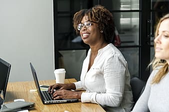 Woman in white long sleeve shirt using laptop computer