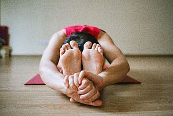 Person wearing red sleeveless top doing yoga