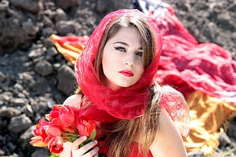 Woman wearing red scarf holding red tulips